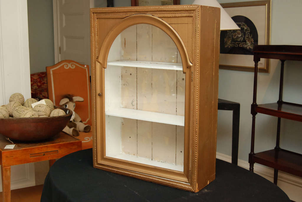 Gold Tramp Art hanging cabinet with white painted interior and two shelves. Glass door.