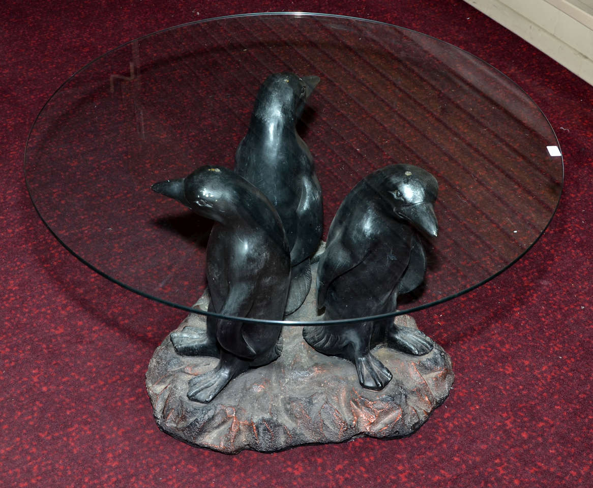 1970's coffee table with base in resin representing three penguins ant top surface in glass.