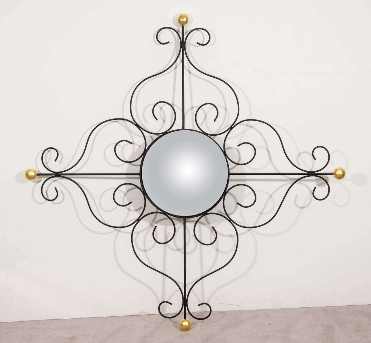 A vintage convex wall mirror with black scrolled iron frame in French modern style with 18-karat gold leaf ball accents.