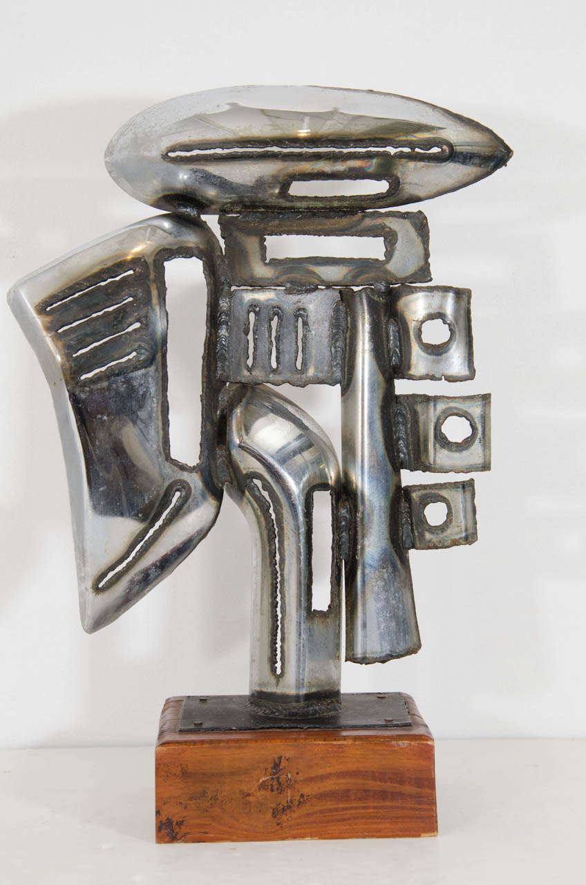 """A vintage sculpture made of chrome car parts and mounted on a wooden cube base.  Illegibly signed. The signature appears to have the first initial """"T"""" and the last initial """"P.""""  Good vintage condition with age appropriate wear."""