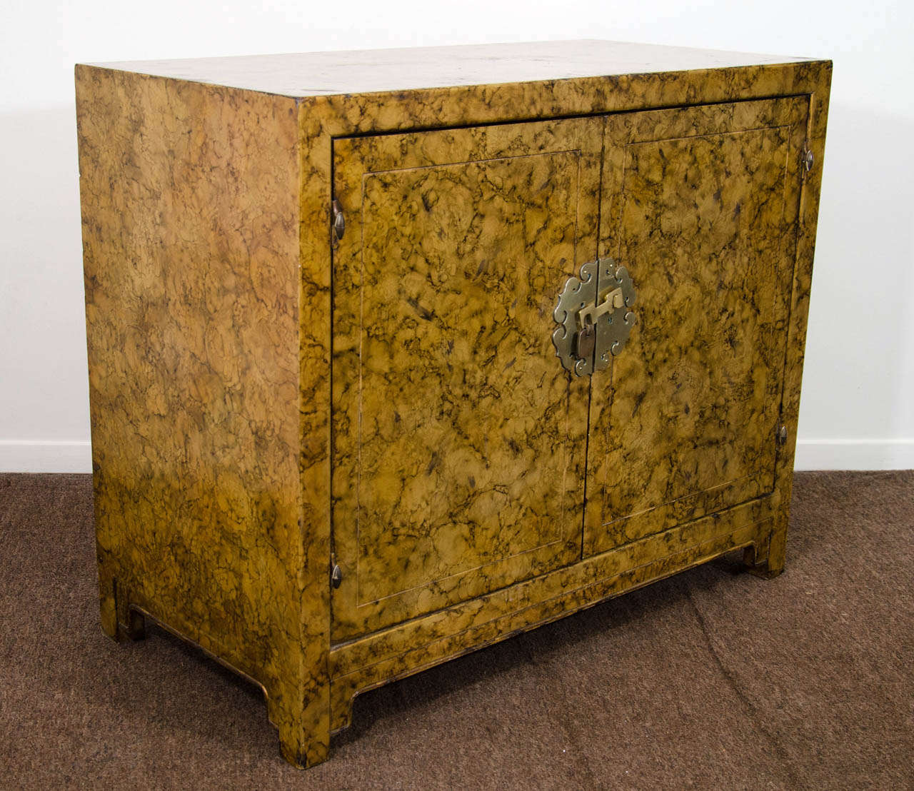A vintage Asian-inspired two door cabinet with brass detailing and Faux tortoise finish.   Vintage condition with some wear around the edges.  There are some nicks and scratches along with small cracks to the surface.