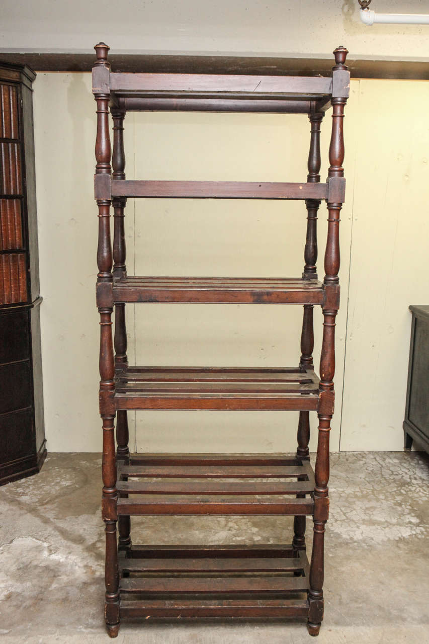 Tall country oak étagère with six slated shelves. Used for storing linens to and displaying books and accessories.