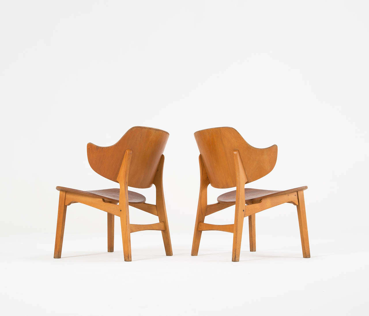 Lounge chairs in plywood, by lb Kofod-Larsen, Denmark 1950s.   The distinctive feature of this pair of plywood easy chairs is its beautifully curved large back which continues in the armrests in one piece. The beech and teak really compliment each