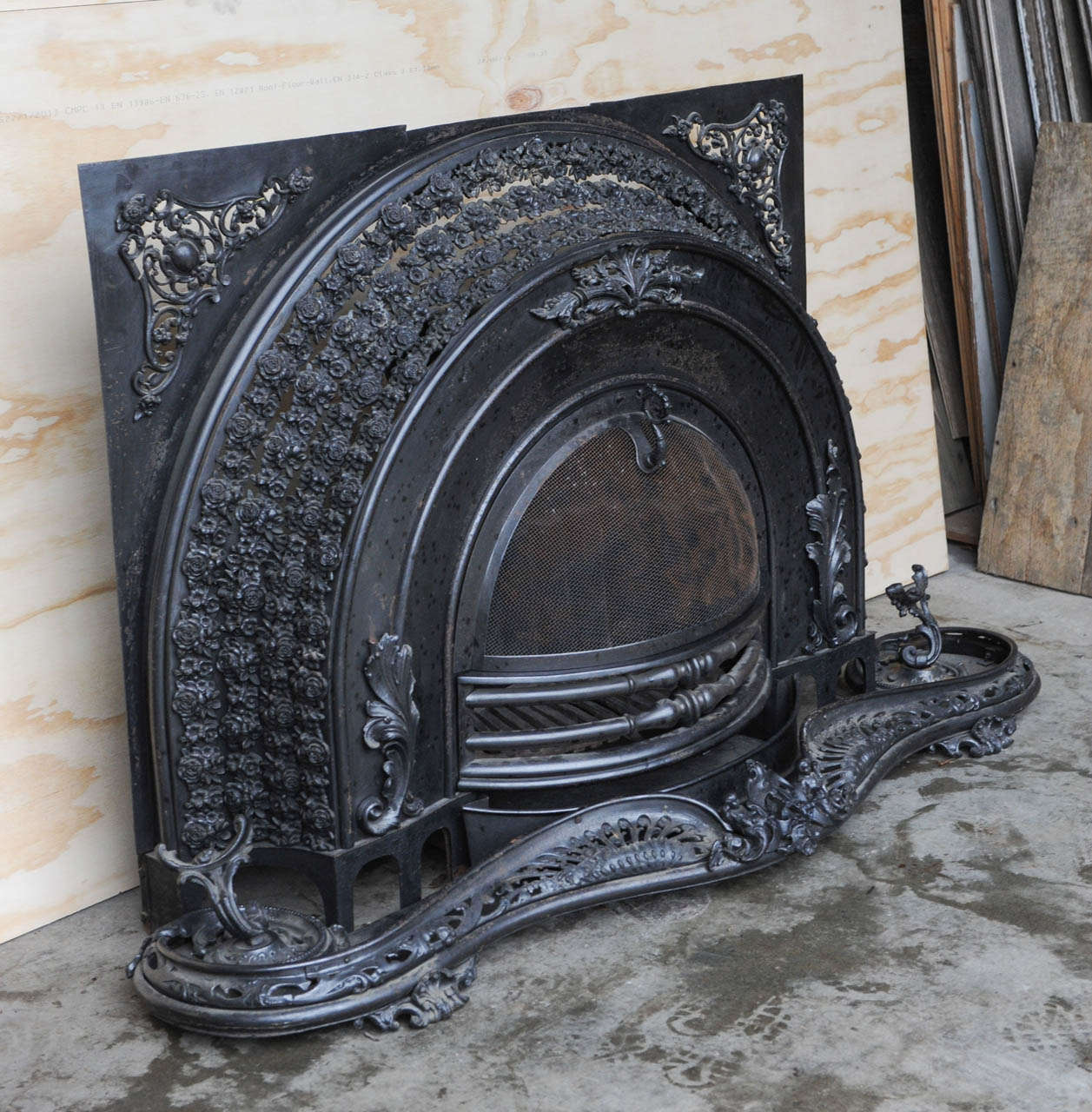 Arched shape, complete with it's original scrolled fender and crate insert. The wrought iron base with scrolled feet. Great Steampunk look. We bought it form a Amsterdam canalhouse, it could also work well in a modern environment.