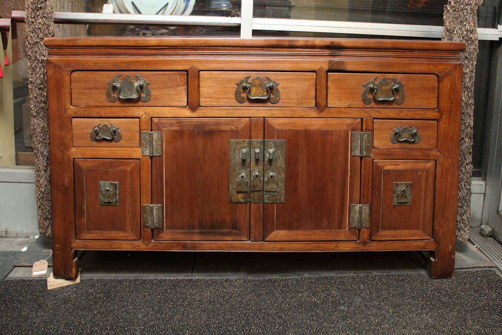 A Chinese elm sideboard with multiple drawers and two doors from the late 19th century. This Chinese sideboard was made in elmwood in an unusually narrow shape, and adorned with brass hardware. The sideboard features two center doors, surrounded by
