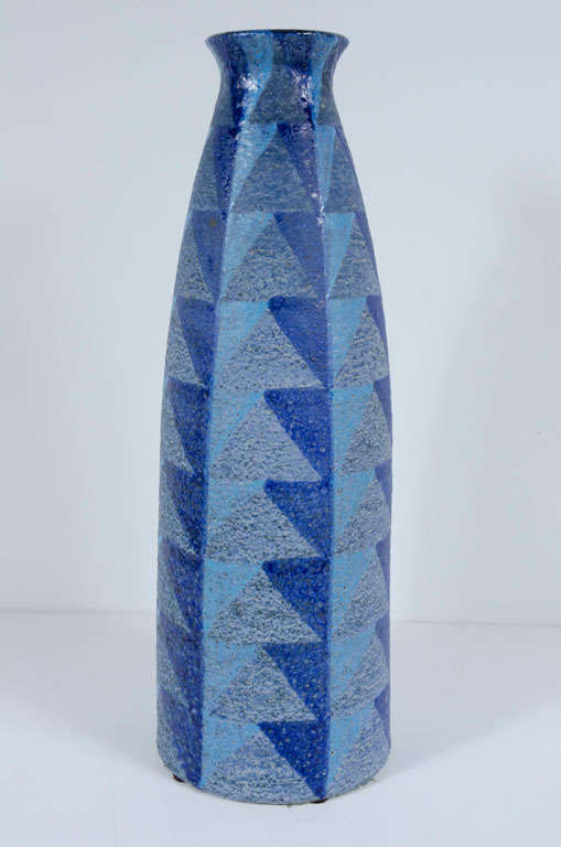 A tall ceramic vase with a mottled glaze geometric design in blues and greys to the exterior and a sleek high gloss black glaze interior. By Bitossi. Italian, circa 1950.