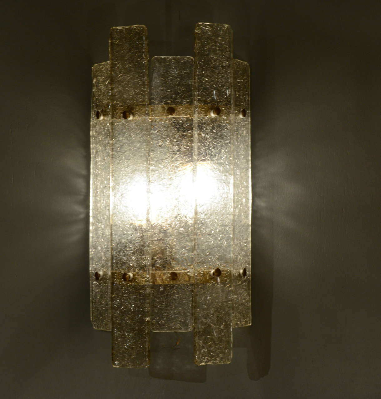Set of nice and enlightening circular brass wall sconces covered by two sizes textured murano