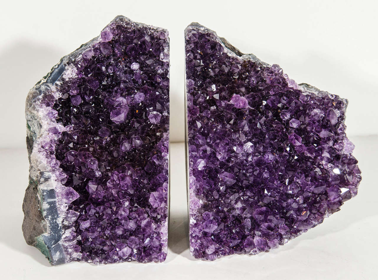 Pair of outstanding large amethyst geode bookends and/or sculptures. The specimens features rough stone edges in hues of slate with variant green edges, and a multitude of vibrant amethyst crystalized spikes in deep purple.  Each bookend measures