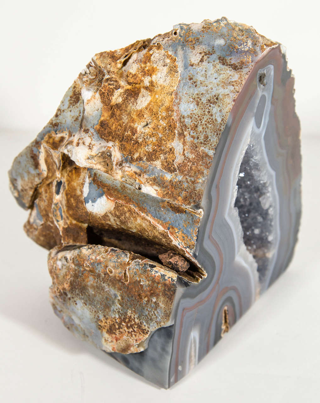 Gorgeous agate stone specimen sculpture with polished front and rough edges. The stone piece has variant hues of grey, browns and black tones with a grey fine crystalline center. Makes a great decorative object or as a bookend.