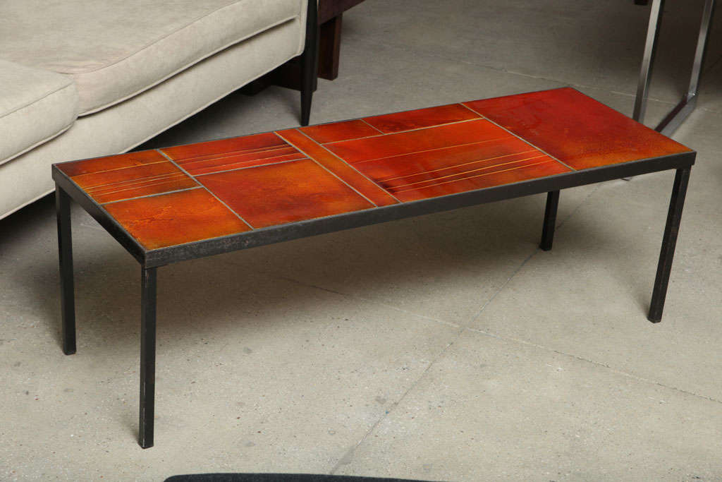 This table has a slim profile and features amber-hued tiles with a seemingly inner glow, arranged of subtle variations and nicely balanced.