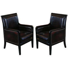 A Pair of Ebonized and Leather Upholstered Chairs
