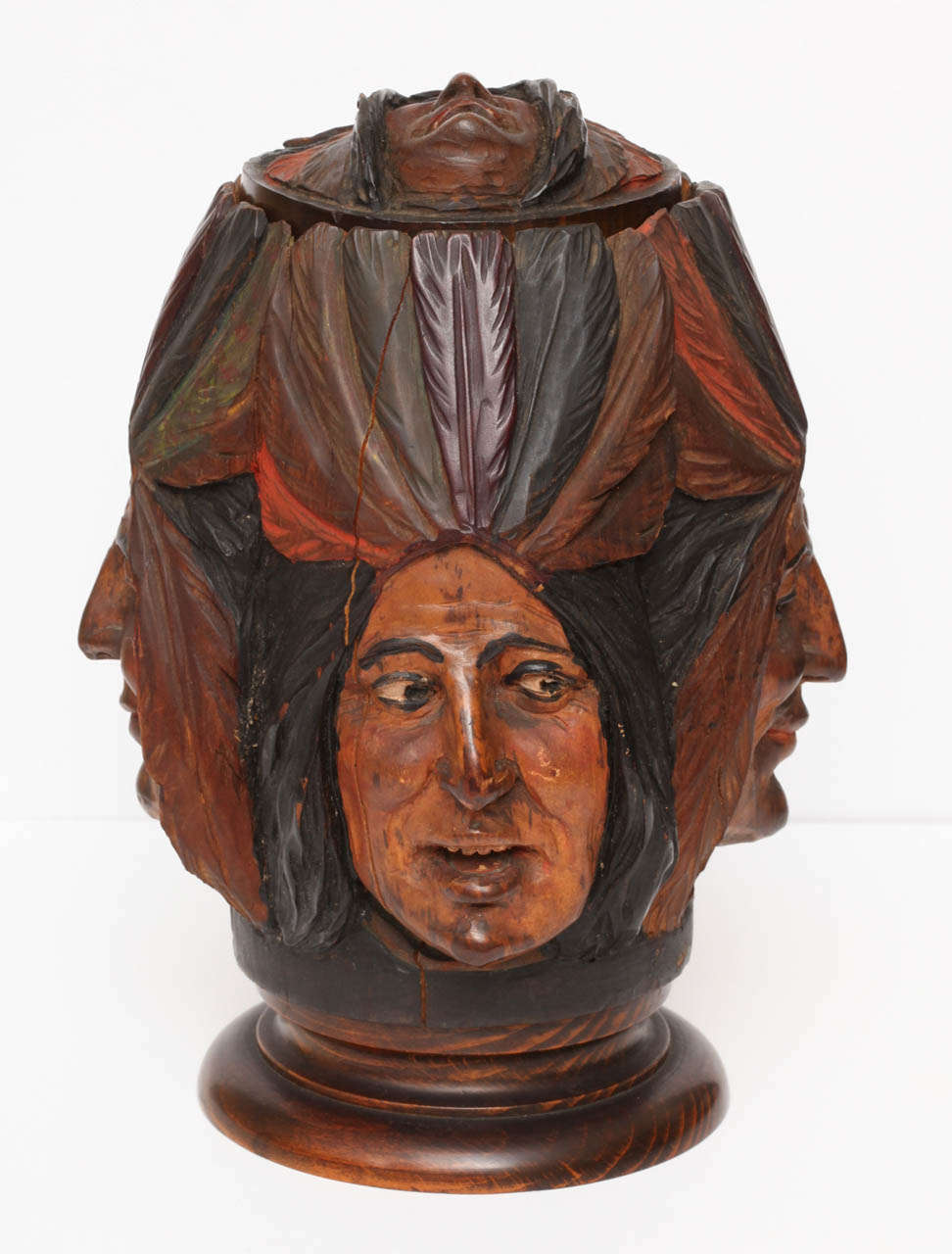 Various hand-carved Indian Chief faces adorn the sides of this tobacco jar. Very detailed with interesting facial expressions and each wearing a colorful feather headdress. Fitted with a lidded top which also has an Indian face carved onto the
