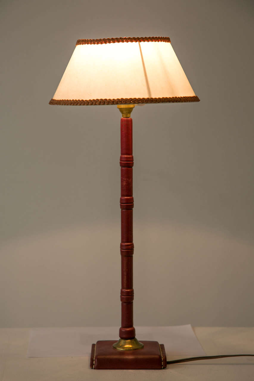 Table lamp by Jacques Adnet (1900-1984) entirely covered with saddled stitched red leather. Tubular trunk and two sided openwork base jointed by a gold metal strapping. Lamp shade with flared sides. Wired for continental Europe use.