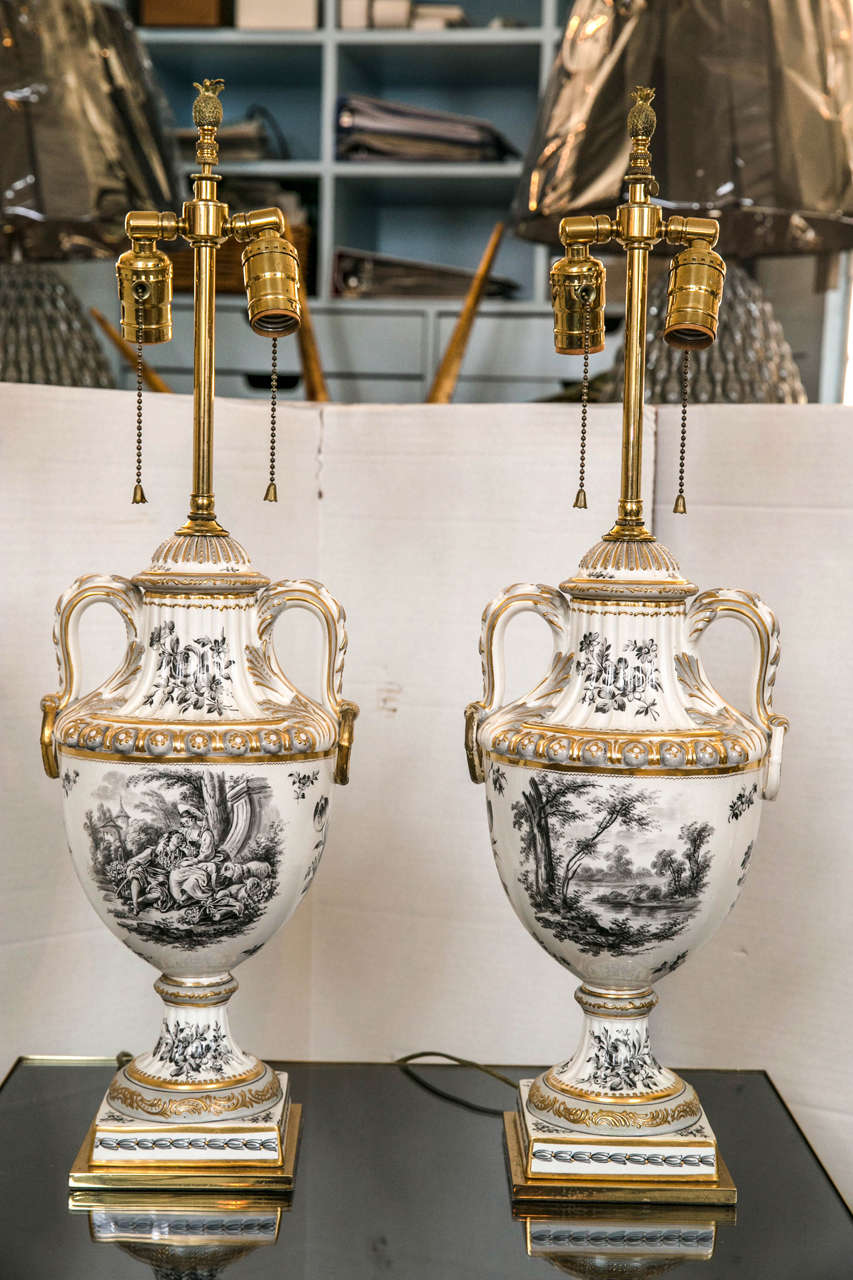 A pair of porcelain urn vases with a black and white toile style decoration and gilded embellishment. The square bases are brass and all hardware is brass. No shades are included.
