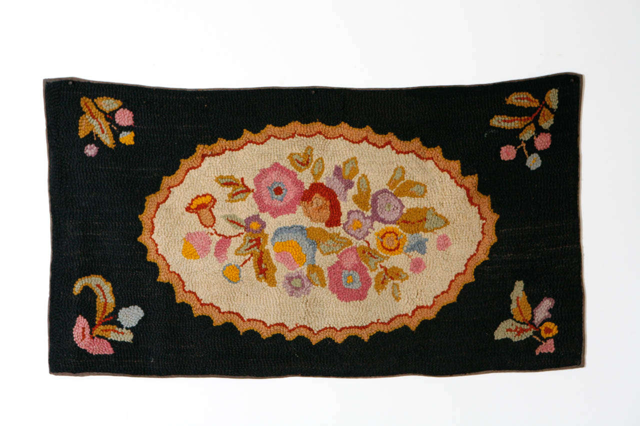American hand hooked wool rug of brightly colored floral bouquet on oval, pale gray background, framed in black wool surround, with small floral motifs in each of the four corners.