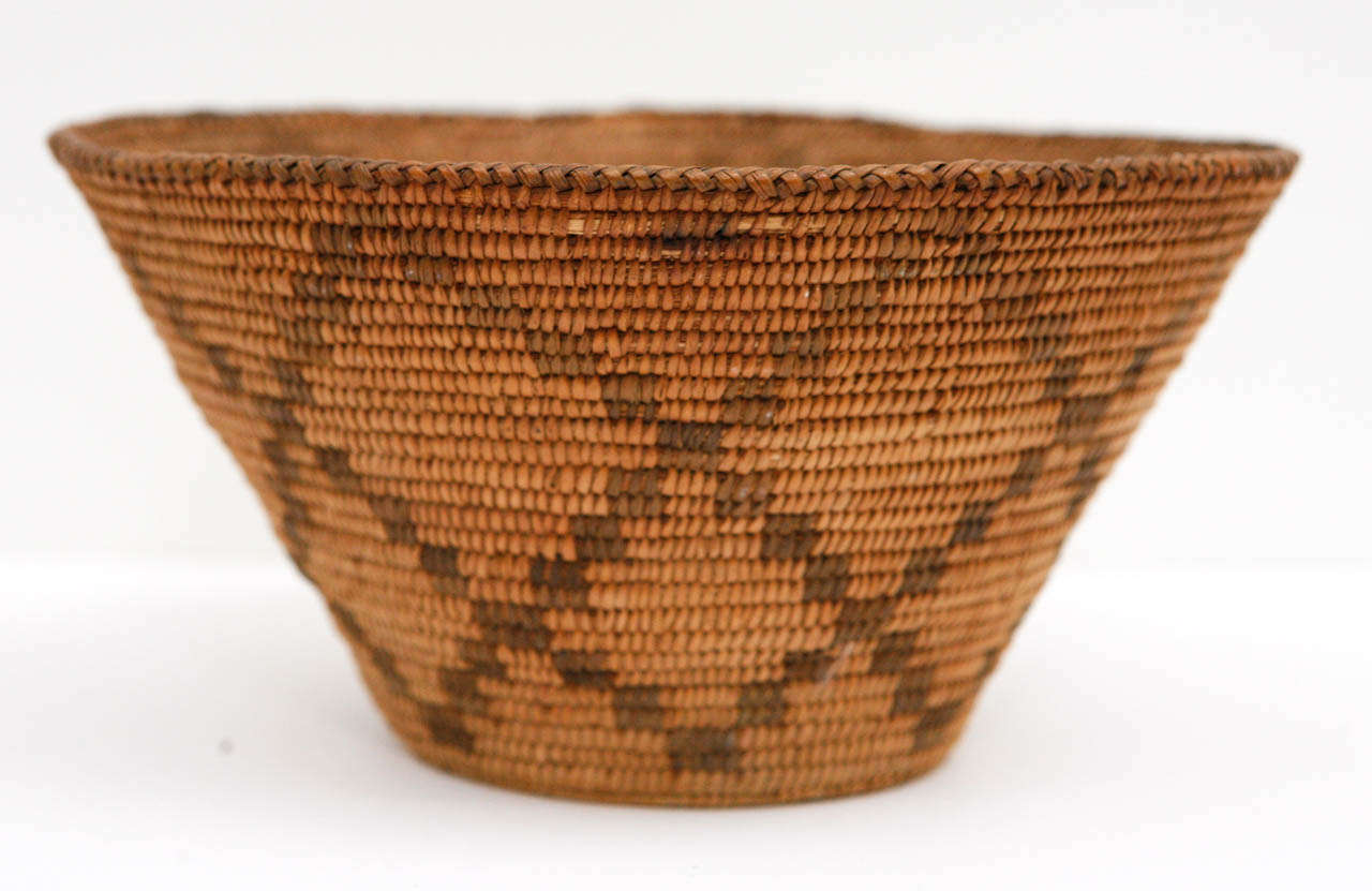 A fine Apache or Pima Native American basket in good condition with attractive dark golden patina. With minor losses. Likely made in late 1890s-early 1900s. Handmade of willow and devil's claw.