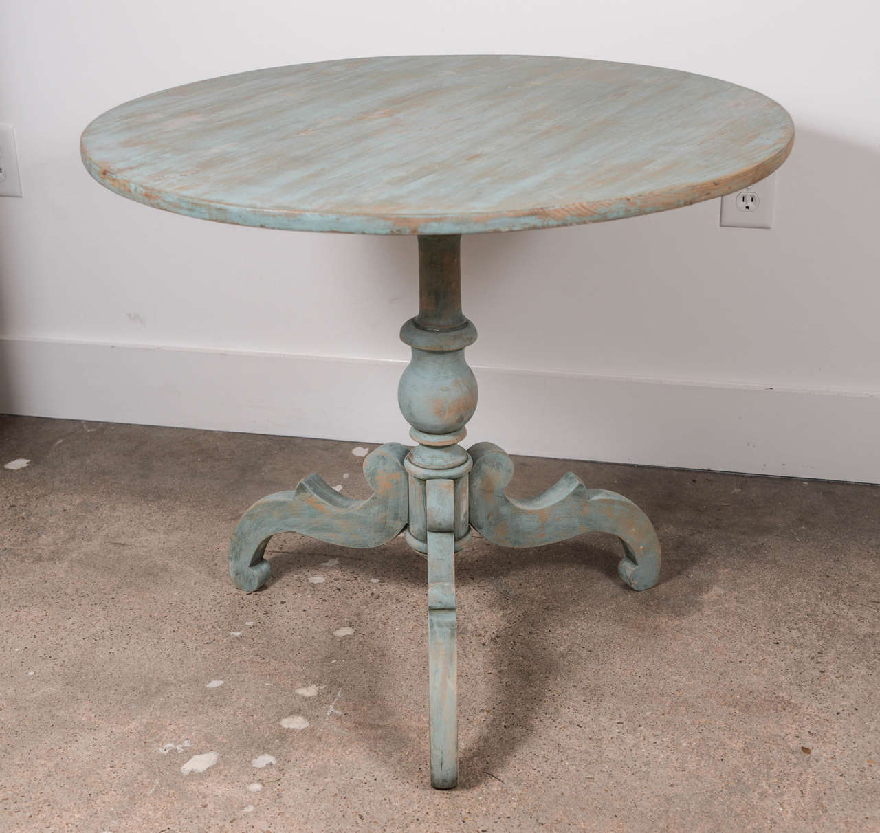 Decorative blue painted 19th century tilt-top pedestal table with a turned base supported by 3 scrolled feet.