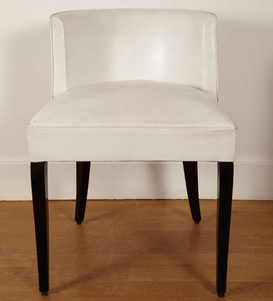 Pair of black varnished and white leather covered chairs.  Square curved feet.  Curved back.