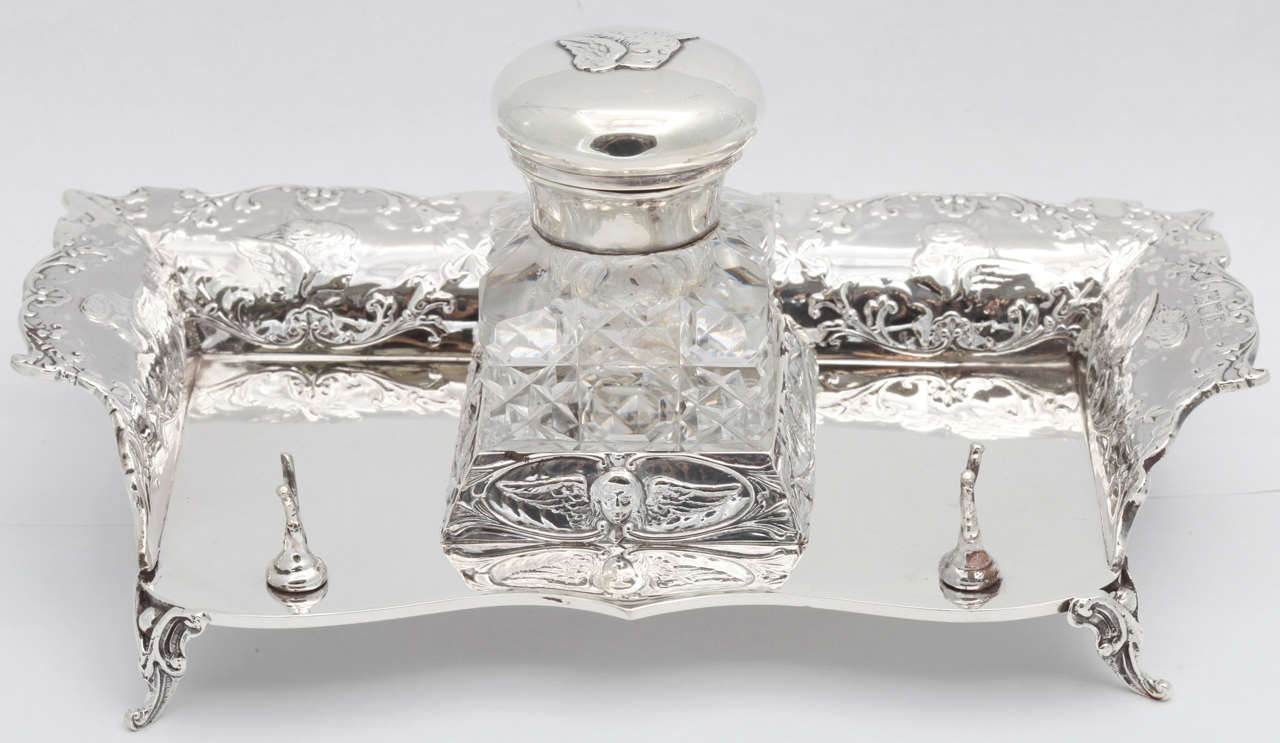 Outstanding, Victorian, sterling silver, footed inkstand with sterling silver-mounted crystal inkwell, London, 1901, William Comyns, maker. Designed with Joshua Reynolds' cherubs motif. Motif is on the sterling silver inkstand and continued on the