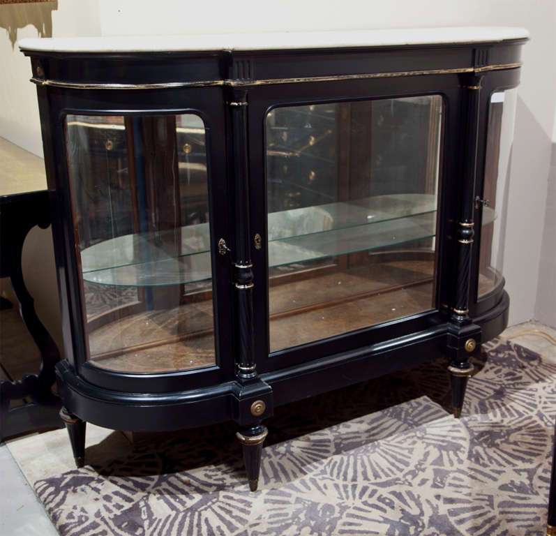 French Directoire style curio cabinet, circa 1940s, the white half-moon marble atop a conforming ebonized cabinet with glass front, the center door flanked by circular columnar uprights, raised on four tapering bulbous legs. Stamped Jansen.