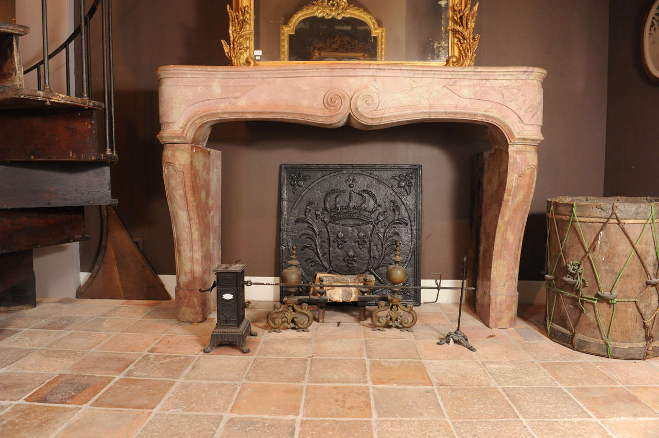 an early 18th c french baroque polished limestone fireplace