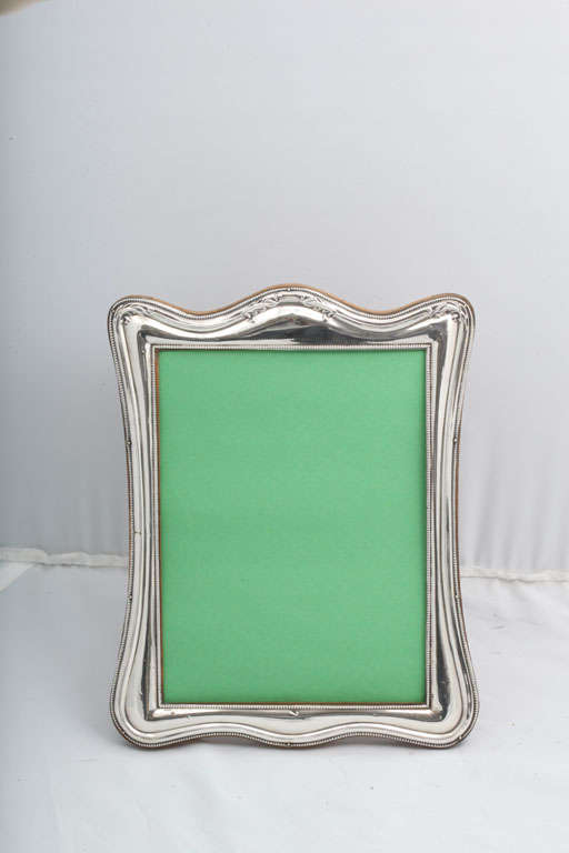 Large, sterling silver, wood-backed picture frame, Birmingham, England, 1921, Gulienetti and Co., Ltd. - makers. Measures 10 inches high (at highest point) x 8 inches wide at widest point x 5 1/4 inches deep when easel is in open position. Holds a