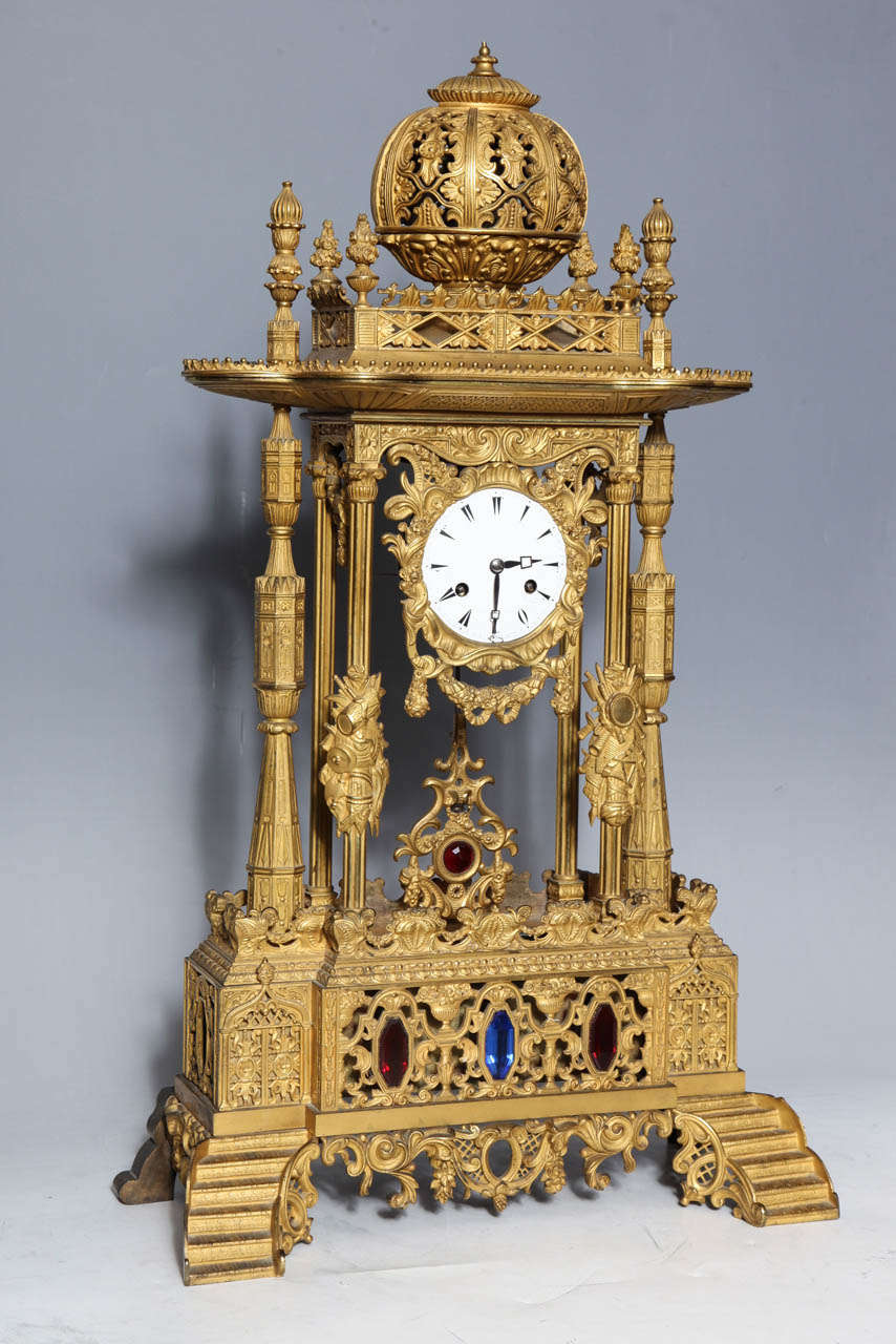 An important antique French orientalist style Jeweled gilt bronze clock made for the Ottoman market. This enameled clock sits within the decorated column's supporting a tulip shaped dome. Swags and wreaths abound, culled from many periods, while