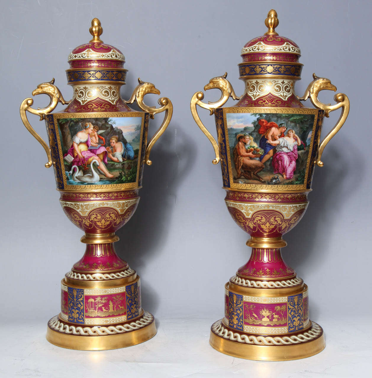A magnificent pair of 19th century royal Vienna covered urns on original stands with double eagle handles depicting neoclassical lovers and cupid. These ornate urns show scenes populated by angelic cupids in beautifully deep landscapes surrounding