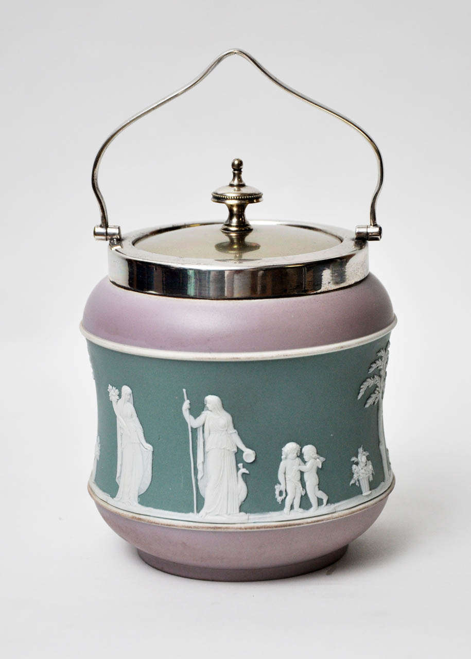 A charming tri-colored lavender and green, trimmed in white biscuit jar, raised white figures of women, cupids and floral encircle the center. Epns silver lid, rim and arched handle. Marked on bottom, Wedgwood, England, Buslem England.