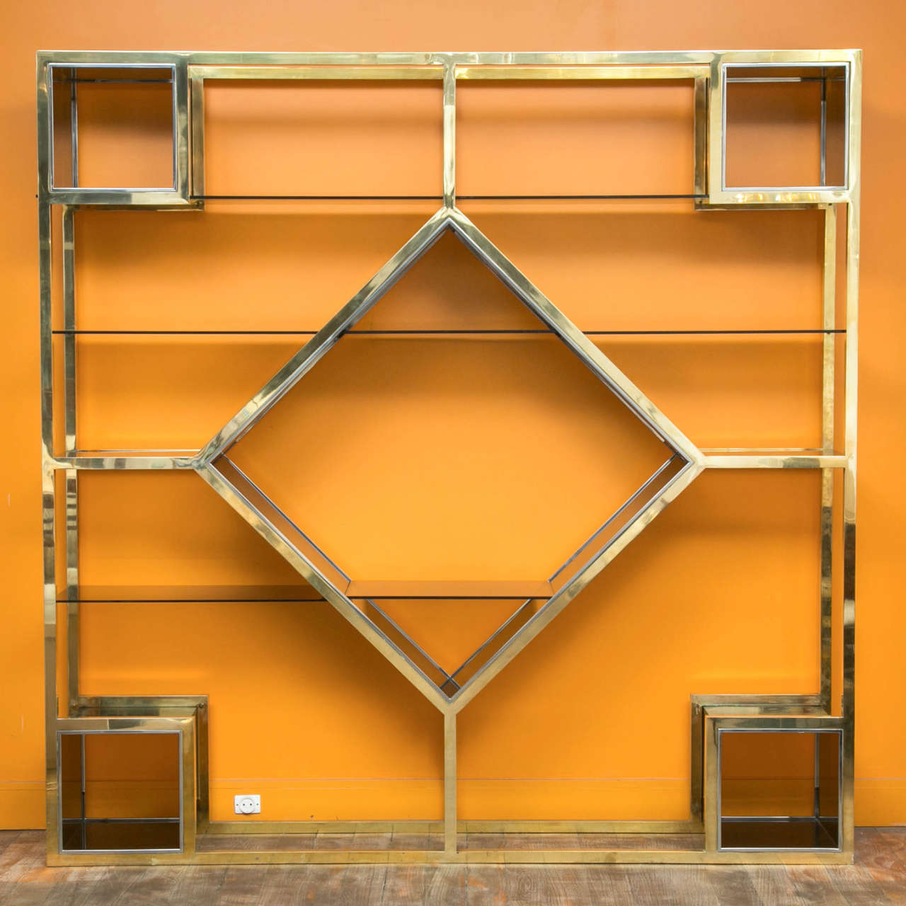 A large metal étagère, polished brass structure, partly chromed.