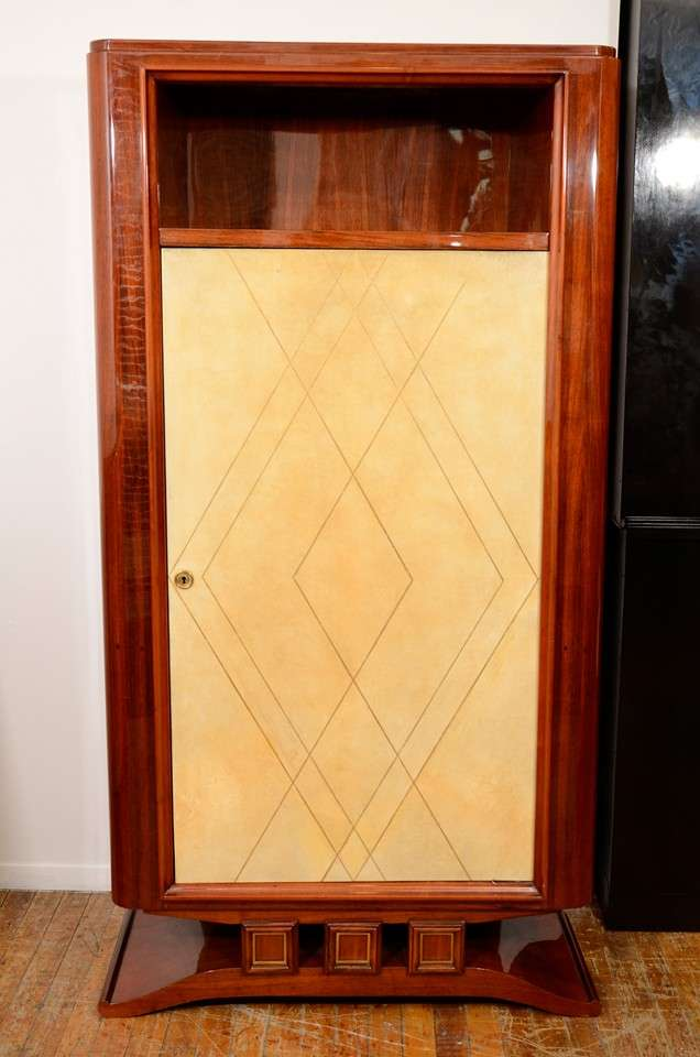 A vintage French Art Deco cabinet in rosewood with a pale parchment door detailed with diamond form gold leafing. The piece has a key-locked, shelved interior.