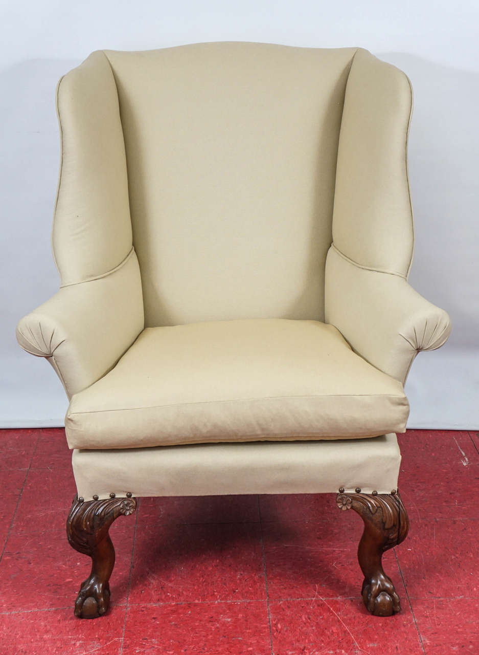Substantial and comfortable wing chairs have carved cabriole ball-in-claw and leaf legs, separate cushions and are upholstered in beige fabric.