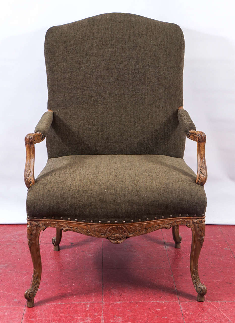 This newly restored antique French Provincial Louis XV fauteuil or armchair has an elegantly hand-carved walnut frame composed of leaves, shells and hearts. The new upholstery is olive velvet.   Arm height: 26.75