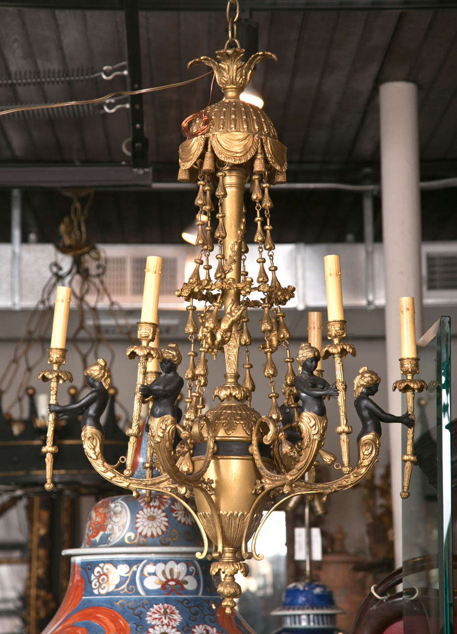 In the anglo-indian style with 6  blackamoors each holding a torch form light, patinated  from their  midsections to their  foreheads, with gilt bronze hair (not turbans). Chains with  small hanging putti above, to the  tent  form top of drapes and