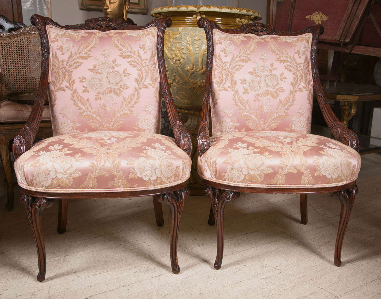An interesting pair of mid century arm chairs  in hand carved mahogany.