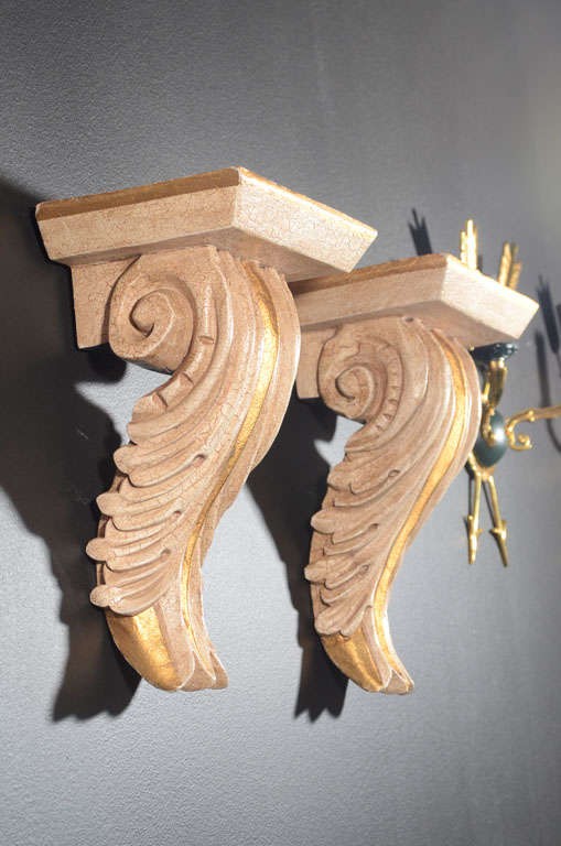 Hollywood Regency wall brackets with classical acanthus leaf design. Hand-carved with crackle pattern Gesso finish and gilt details. Made of plaster coated wood and have a top shelf with fluted and scrolled design.