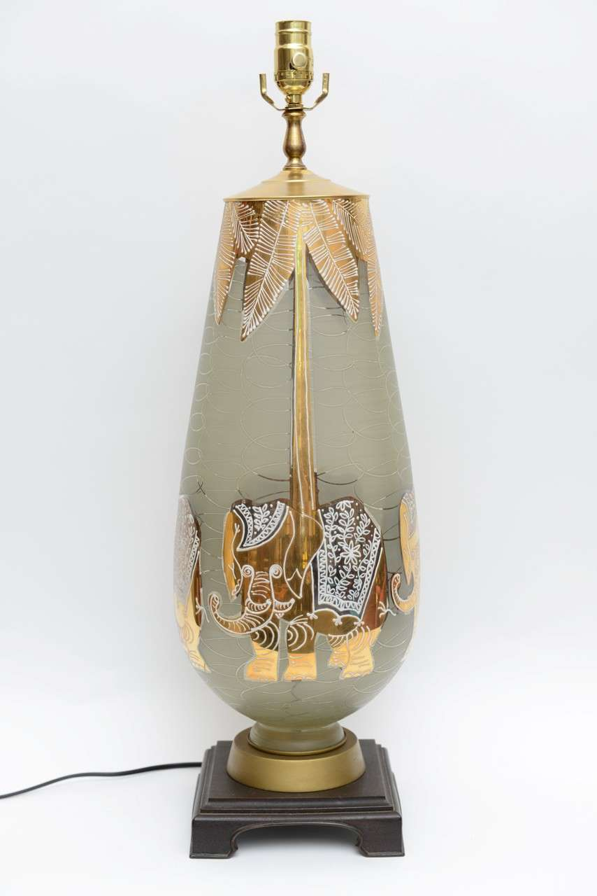 If not Waylande Gregory, certainly channeling his wonderfully elegant humor and playful style, this exquisite tall etched, gilt and enamelled teardrop shaped blown glass table lamp has four magical large gilt elephants around its body with palm tree