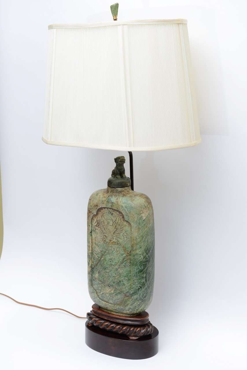 Wonderful scale and presence, an Asian aura and regal stature highlight this table lamp from the 1940s. Large-scale, this beautifully carved snuff bottle shaped jade colored soapstone vessel is itself over 17 inches high and sits mounted on a
