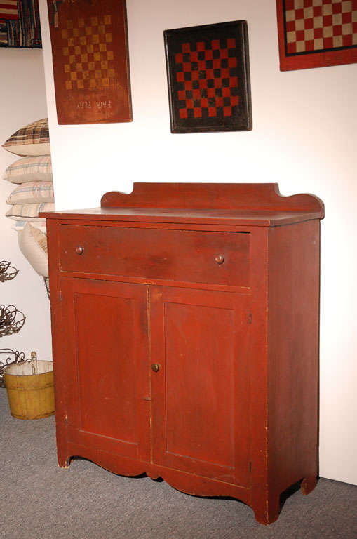 Fantastic form and condition original red painted jelly cupboard with a wonderful scalloped skirt. This Great cupboard has one large drawer over two doors.The surface is super and very strong.The sides have wonder cut out feet too. Great addition to