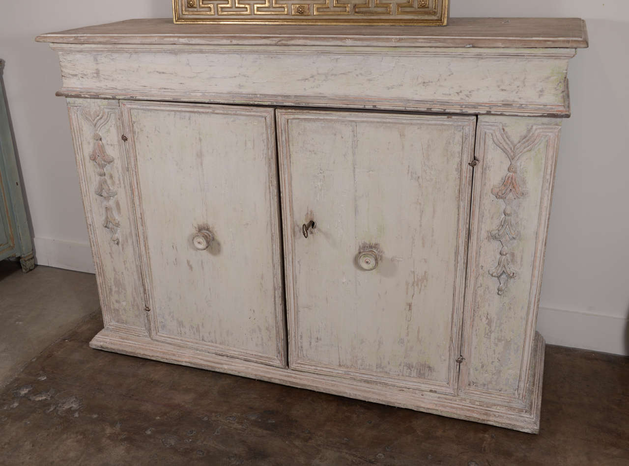 18th century Italian buffet from a Palazzo in Venice. Beautiful intricate carving on panels down the facade of piece and along the perimeters panels. Well weathered original paint. Handsome piece.