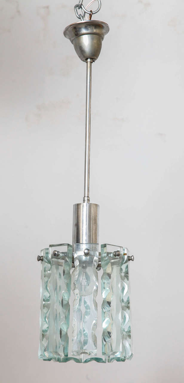 In style of Fontana Arte,clear crystal ceiling light. Nine thick carved pieces hanging on a stainless steel frame.