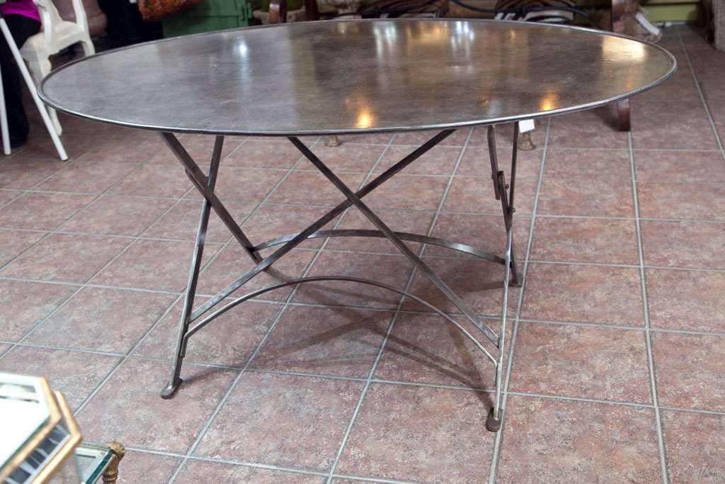 Imported from France folding metal tables, wrought iron campaign style, oval shape. Seats 4 to 6
