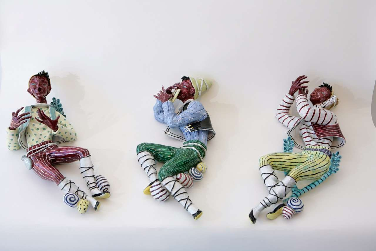 A trio of whimsical ceramic minstrels by San Polo, designed to be wall hung. Dimensions are given below for the figure on the left. The central figure playing the pipes measures 10.5
