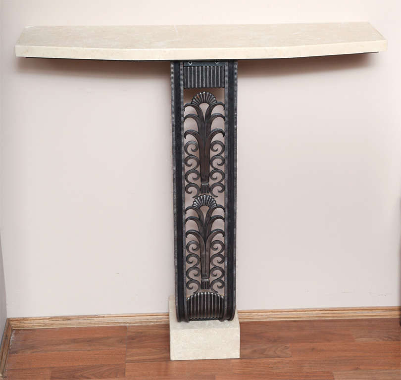 Art Deco style console in the manner of Edgar Brandt.  Wrought iron, with travertine top and base.  Measures: Height 37 1/2 in, length 37 1/2