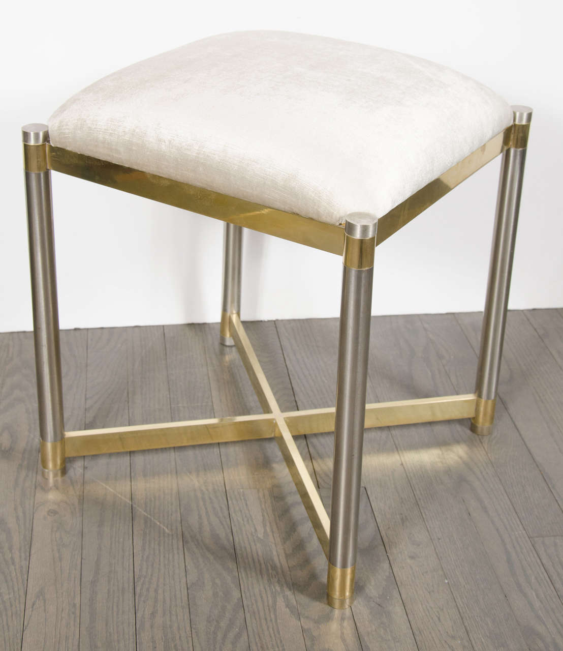 This sophisticated Mid-Century Modernist X-Form Stool in the manner of Karl Springer was realized in the United States, circa 1970. It features brushed cylindrical chrome legs banded in brass with a brass x-form support at its base and an