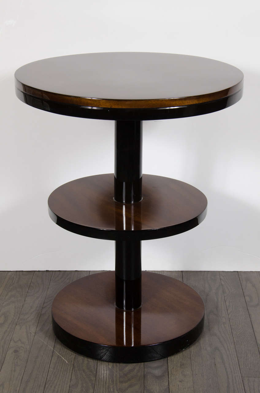 This stunning and graphic pair of Art Deco Machine Age end/ side tables were realized in the United States, circa 1935. They feature book-matched round walnut tops circumscribed by black lacquer and connected by a cylindrical rod in black lacquer.