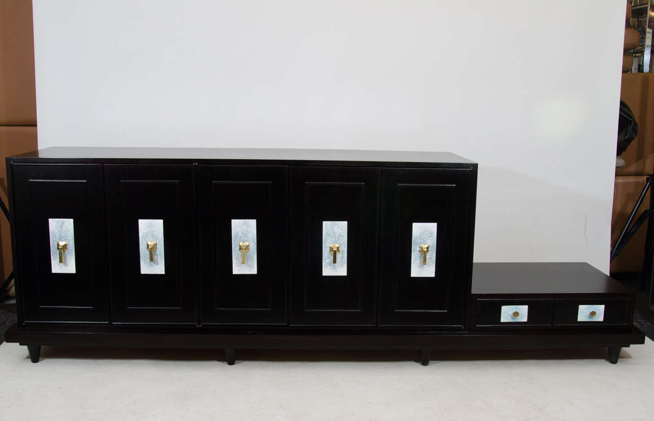 Elegant credenza with an attached low table by Renzo Rutili. The credenza is in an ebonized finish with beautiful enameled escutcheons accented with brass door pulls. The credenza has one cabinet fitted with drawers. Please contact for location.