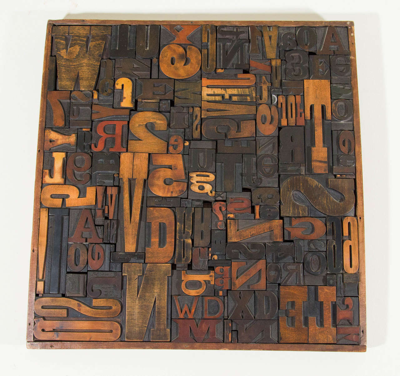 A vintage wall sculpture composed of letterpress printing blocks, produced circa 1960's - 1970's, with a variety of letters and numbers in a wooden frame. Good vintage condition with age appropriate wear.   Second letterpress printing blocks wall