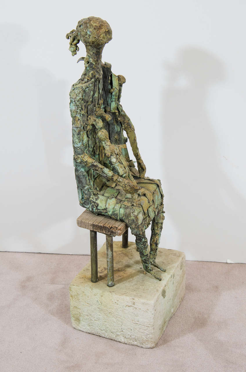 A Brutalist style sculpture in copper of a mother seated on a wooden bench with her child and mounted on a stone pedestal base. Initials