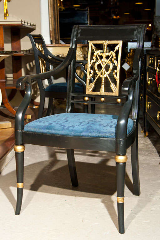 A set of Eight Maison Jansen style ebonized and paint decorated arm chairs. All have French back-splat design with arrows running through a ribbon bow. Supported by a bamboo style leg. CAN BUY ONE.